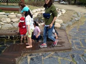 asian children romping around a stream